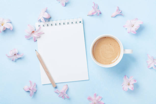 notebook, cup of coffee and pink flowers on blue pastel background top view. fashion woman working desk. spring to do list. - spring fashion stock pictures, royalty-free photos & images