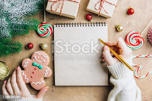 istock Notebook in the center of cute Christmas decoration: gift box, christmas balls, gingerbread man, fir tree branch, cande cane. Female hand writing in notebook. Flat lay. Top view 1188281081