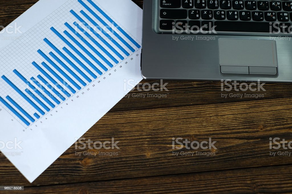 Notebook laptop computer and financial graph on white paper on working table, business planning vision and finance analysis concept. zbiór zdjęć royalty-free