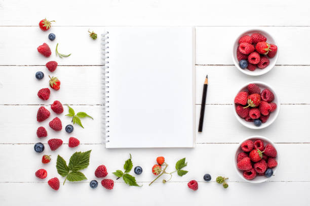 Notebook mock up, pencil and fresh berries on white wooden background . stock photo