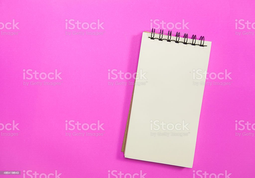 notebook on pink background. stock photo