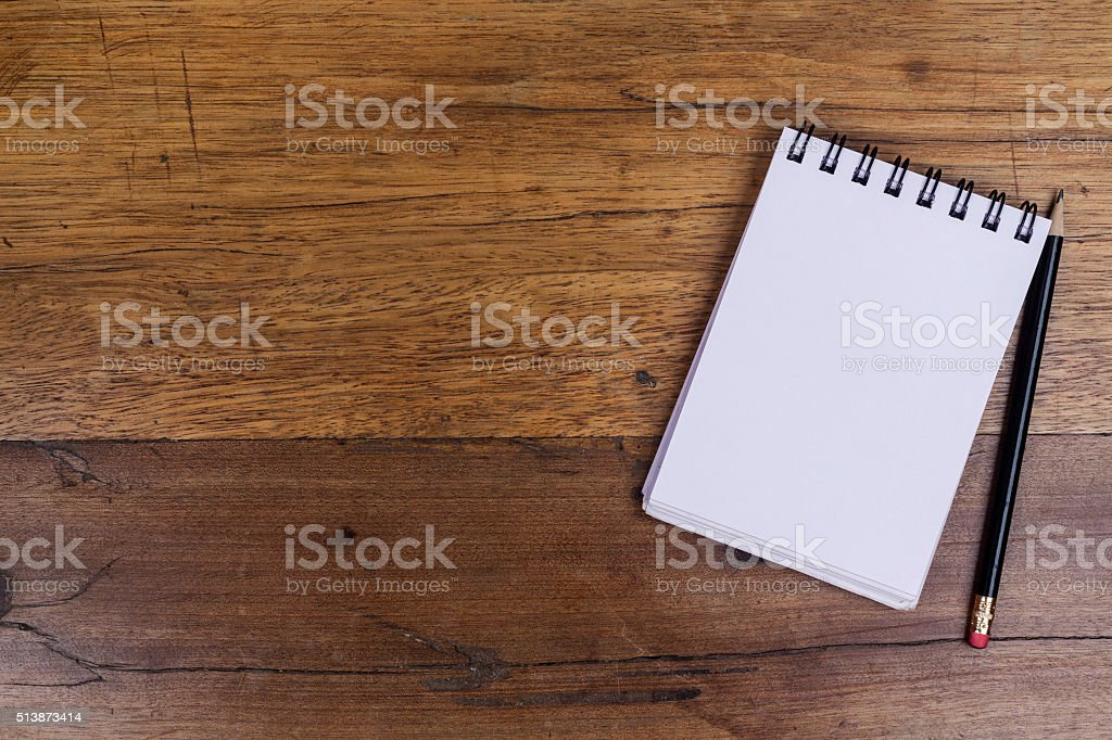 Notebook on right side of wooden table with pencil aside stock photo
