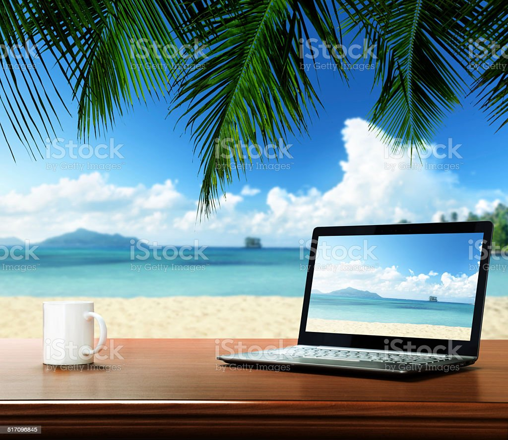 notebook on table and tropical beach stock photo