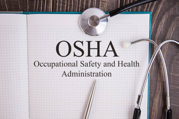 Notebook page with text OSHA Occupational Safety and Health Administration, on a table with a stethoscope and pen, medical concept. stock photo