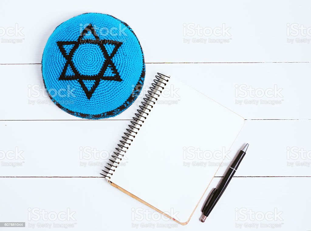 Notebook, pen and blue kipa on a white wooden background stock photo