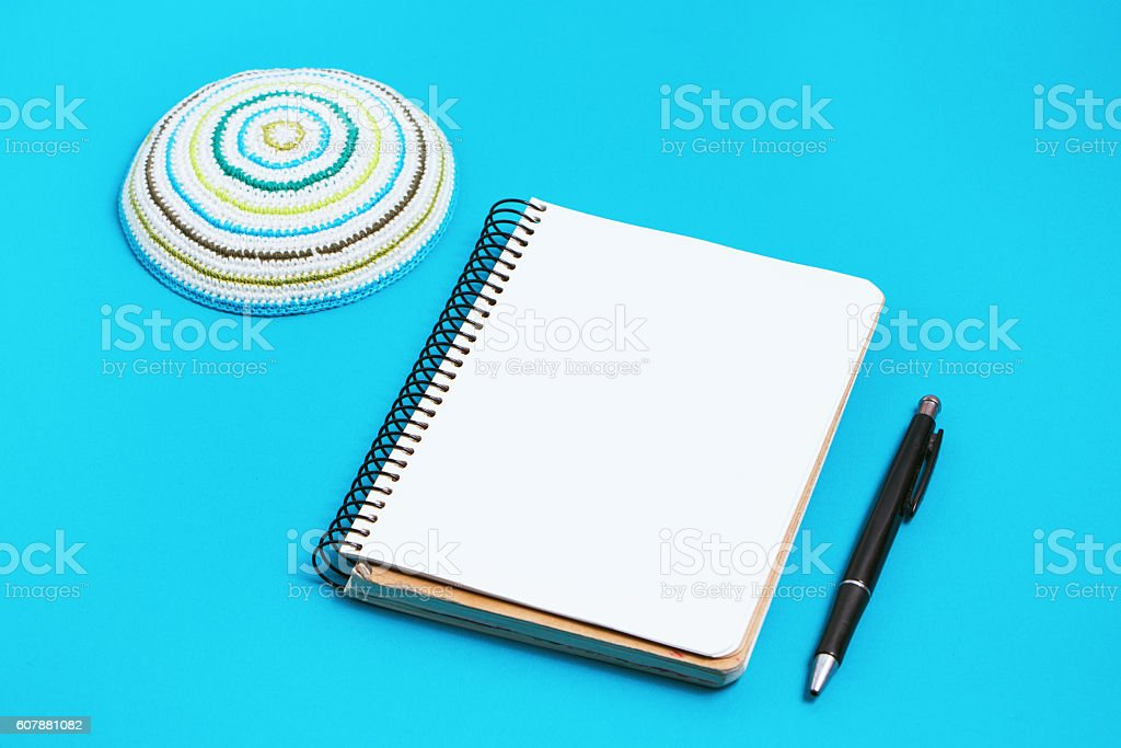 Notebook, pen and kipa on a blue background. Jewish New stock photo