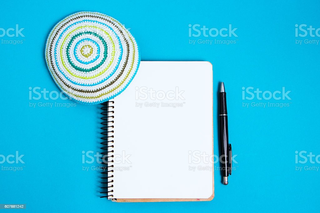 Notebook, pen and kipa on a blue background, top view stock photo