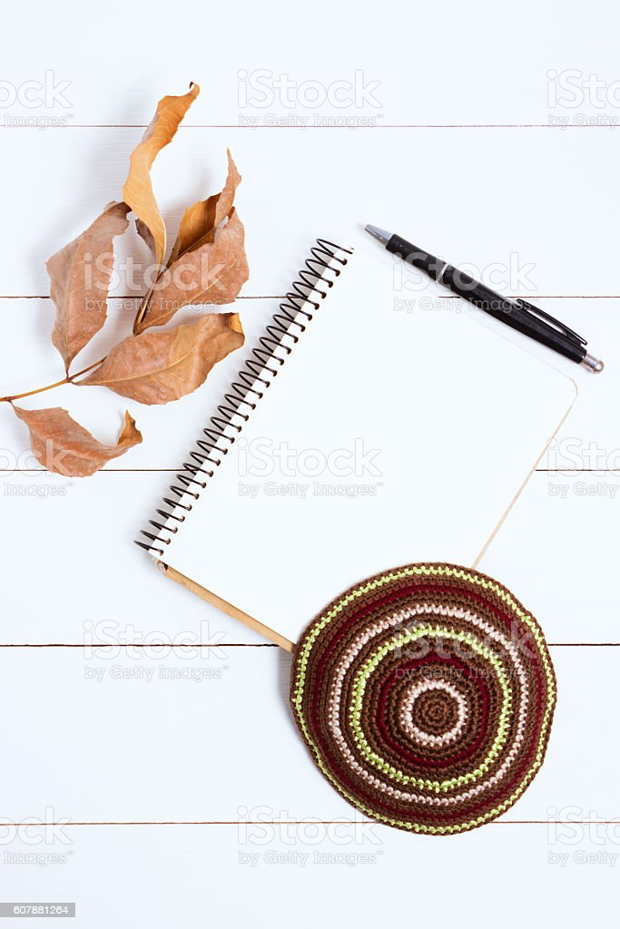 Notebook, pen and kipa on a white wooden background, top stock photo