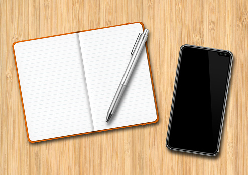 Notebook, pen and smartphone on a wooden desk