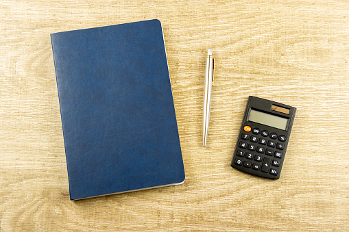 istock Notebook, pen, calculator on a wooden background Top view, flat lay 1213673525