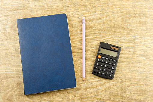istock Notebook, pen, calculator on a wooden background Top view, flat lay 1213673538