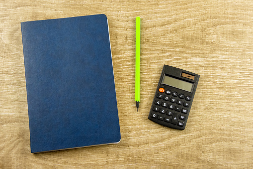 istock Notebook, pen, calculator on a wooden background Top view, flat lay 1213673601