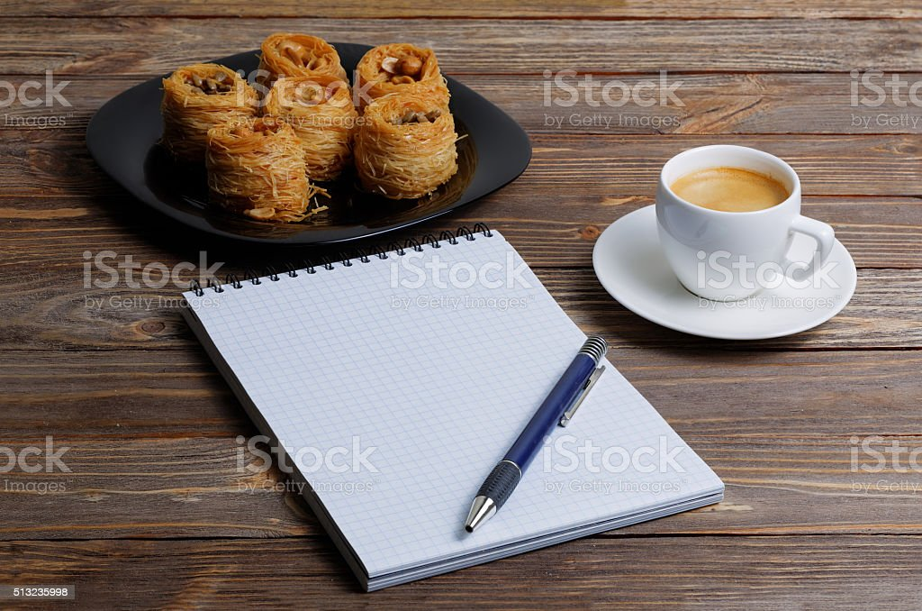 Notebook, pen, cup of coffee and eastern sweets stok fotoğrafı