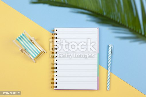 istock Notebook, pen, deck chair on two-color background yellow and blue, copy space, flat lay. Working space of freelancer, top view. Freelance, planning of vacation, travel, sales concept. Horizontal 1207560192