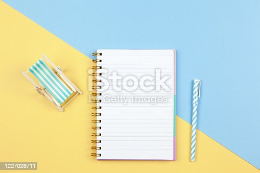 istock Notebook, pen, deck chair on two-color background yellow and blue, copy space, flat lay. Working space of freelancer, top view. Freelance, planning of vacation, travel concept. Horizontal 1227026711