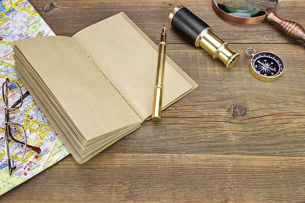 notebook, kugelschreiber, gläser, lupe, cpmpass und spyglass auf holz - kompass wanderkarte stock-fotos und bilder