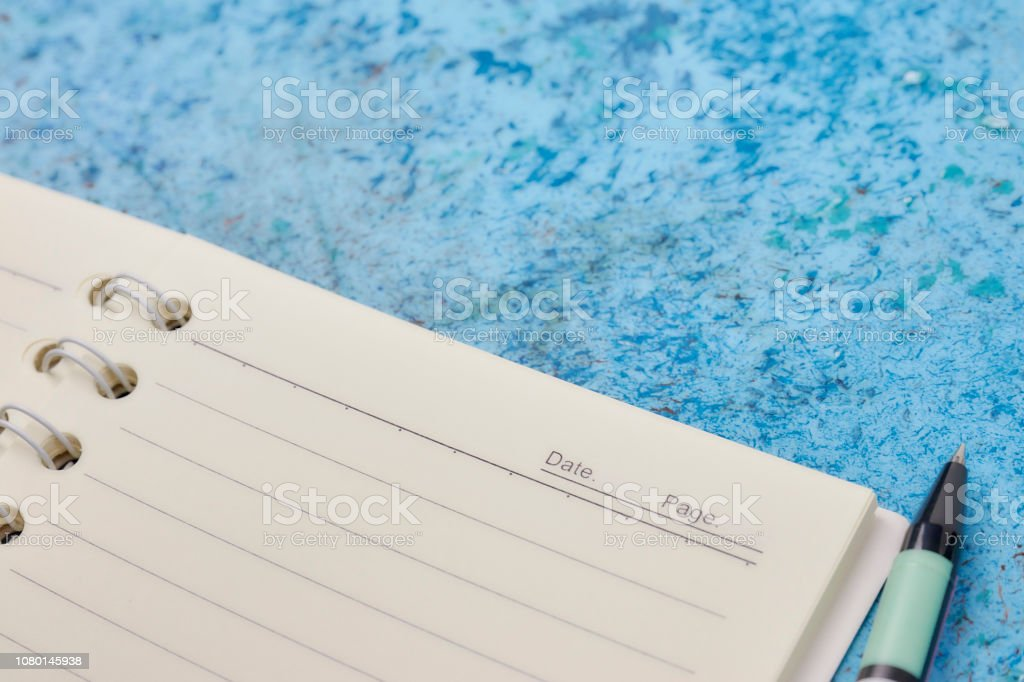 Notebook, pen, on blue abstract background. horizontal view from above. white piece of paper. angular placement of the object. stock photo