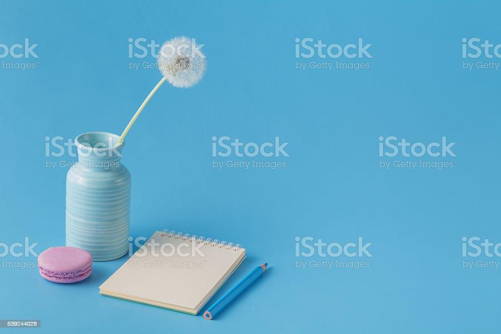 Notebook, pencil, dandelion on blue desk background foto de stock libre de derechos