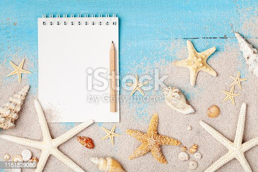 936373320 istock photo Notebook, starfishes and seashells on sand background top view. Planning summer holidays, trip, travel and vacation concept. Flat lay. 1151829080