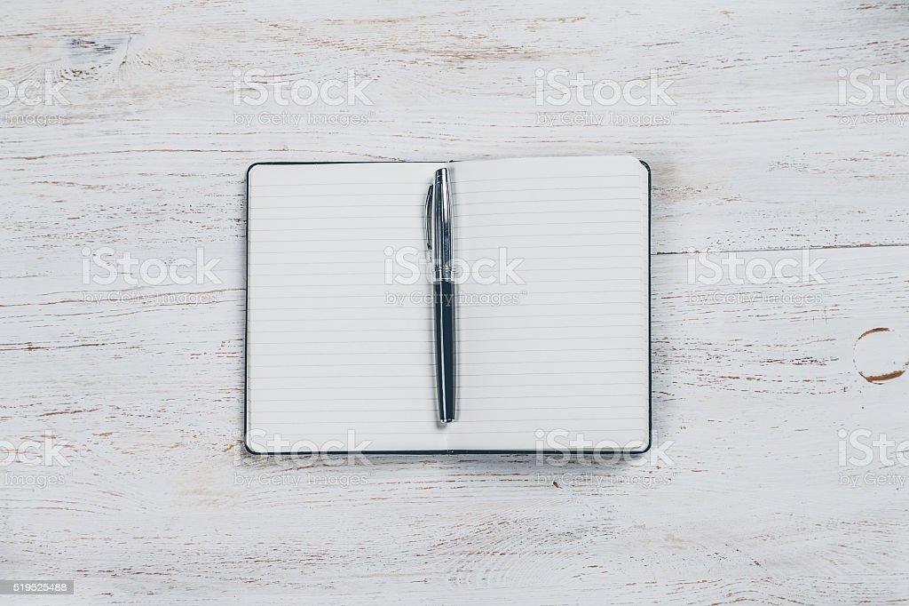 Notizbuch zu schreiben mit einem Stift auf weißem Holztisch – Foto
