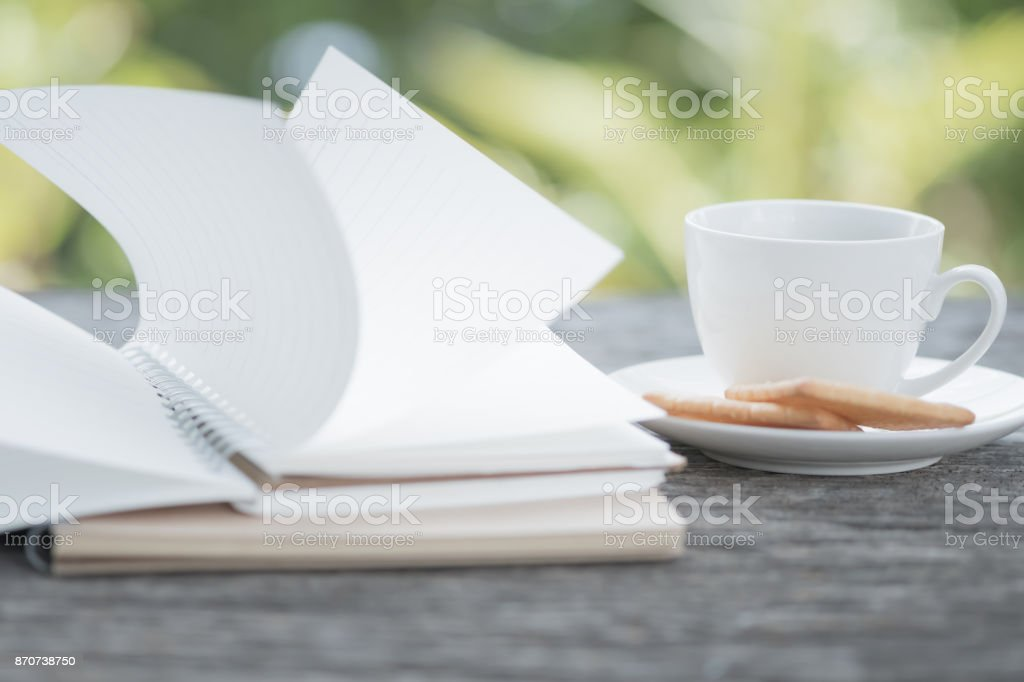 notebook was blown by wind and coffee cup blur picture stock photo