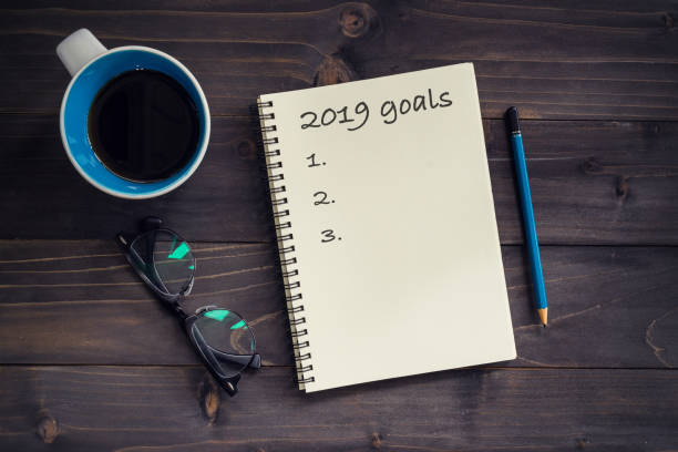 notebook with 2019 goals massage, pencil, glasses and cup of coffee on wood background. - 2019 foto e immagini stock