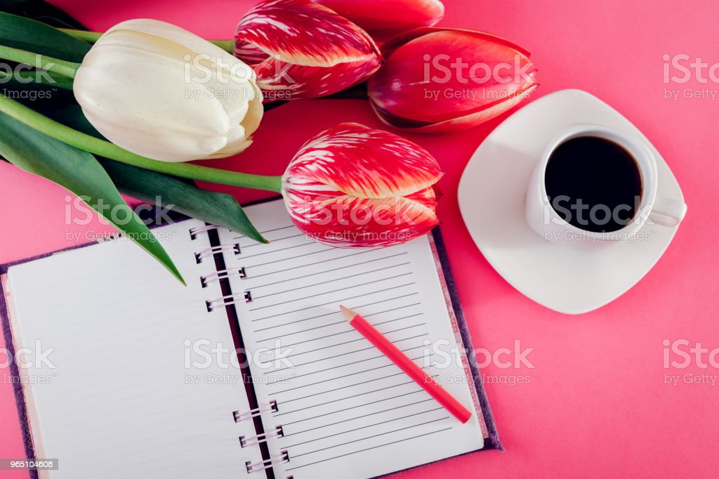 Notebook with a cup of esspresso coffee and fresh tulips on pink background zbiór zdjęć royalty-free