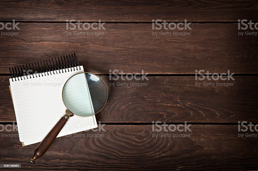 notebook with a magnifying glass on a wooden background stock photo