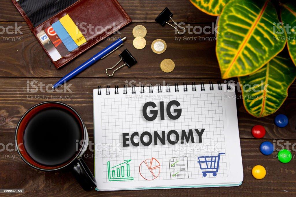 Notebook com um GIG economia de notas sobre a mesa de escritório com ferramentas. Conceito com elementos de infográficos. - foto de acervo