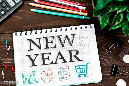 1063751940 istock photo Notebook with a notes NEW YEAR on the office table with tools. Concept with elements of infographics. 1073858448