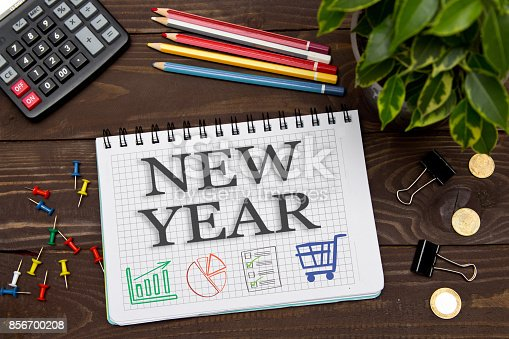 istock Notebook with a notes NEW YEAR on the office table with tools. Concept with elements of infographics. 856700208