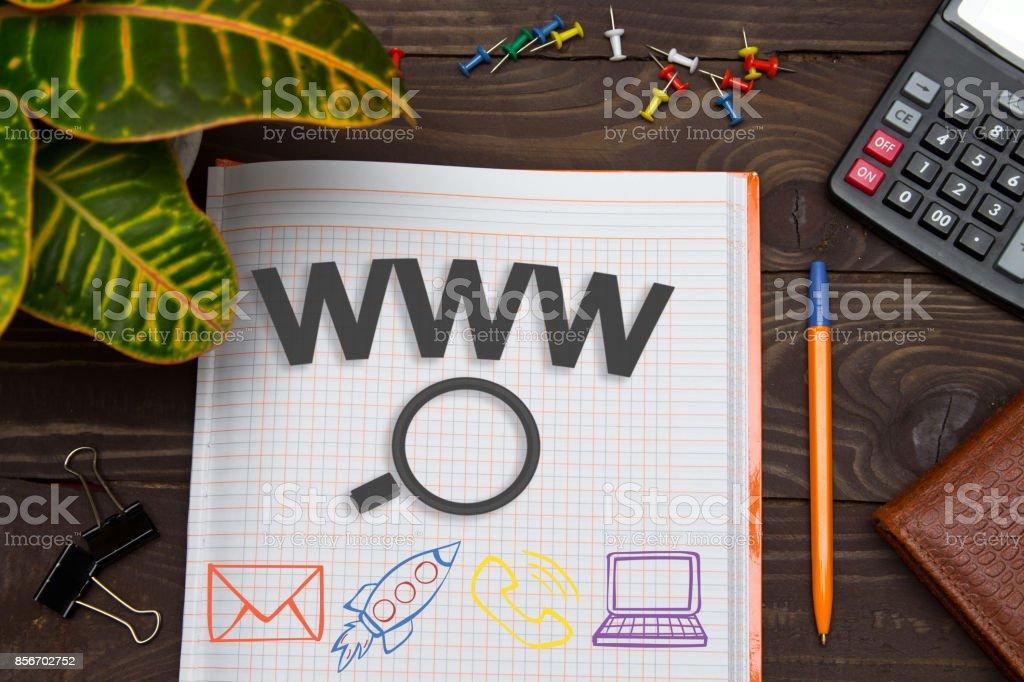 Notebook com uma pesquisas on-line de www notas sobre a mesa de escritório com ferramentas. Conceito com elementos de infográficos. - foto de acervo