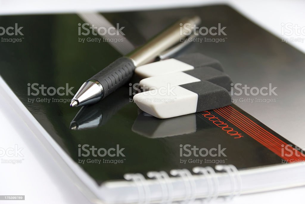 notebook with a pen and erasers