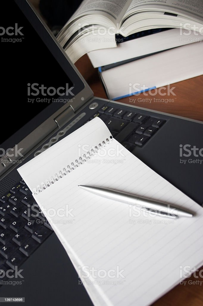 A notebook with a pen sitting on a laptop royalty-free stock photo