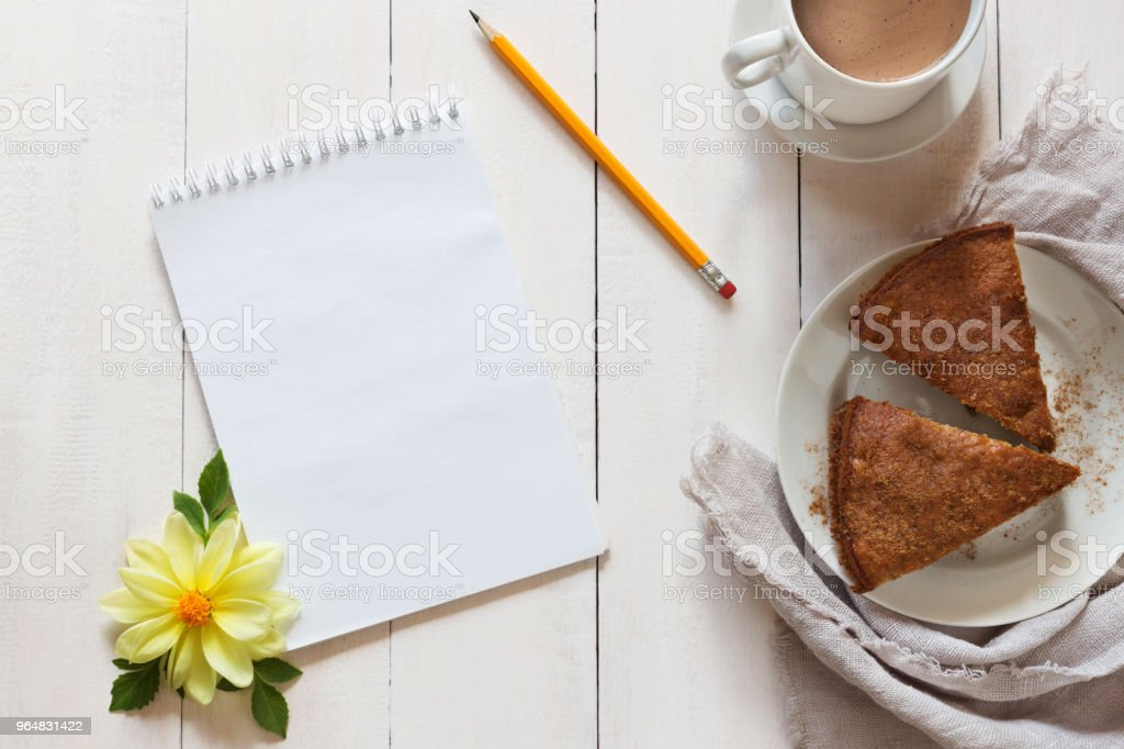 Notebook with a pencil and pie on wooden background royalty-free stock photo