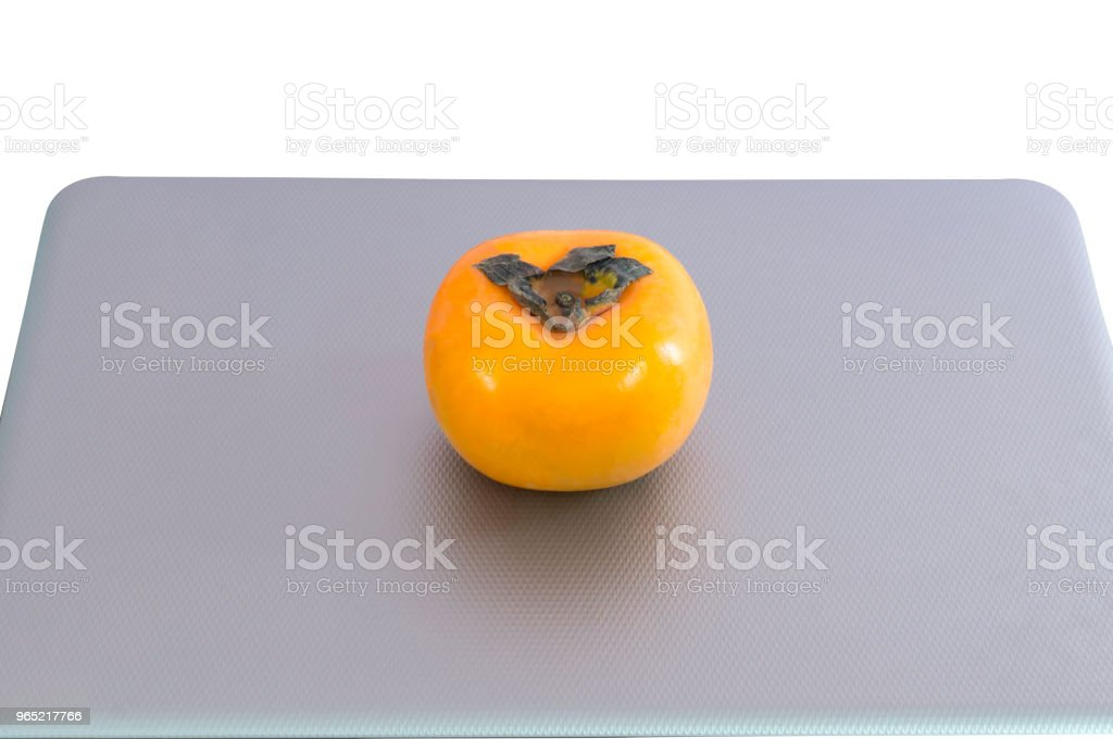 Notebook with a persimmon on it on white background with clipping path royalty-free stock photo