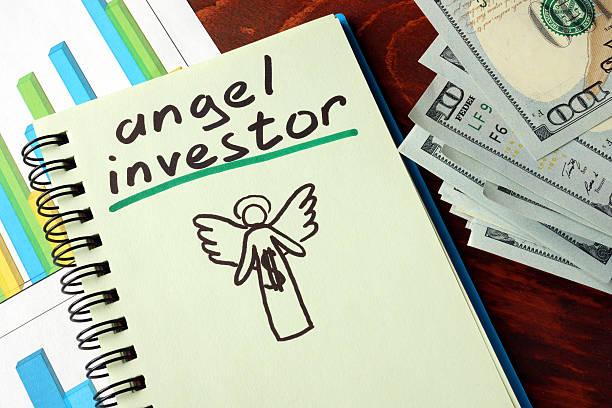 ノートブックとエンジェル投資家の標識に進みます。ビジネスコンセプトです。 - 投資家 ストックフォトと画像