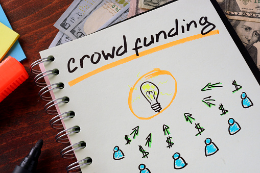 Notebook With Crowd Funding Sign On A Table Stock Photo - Download Image Now