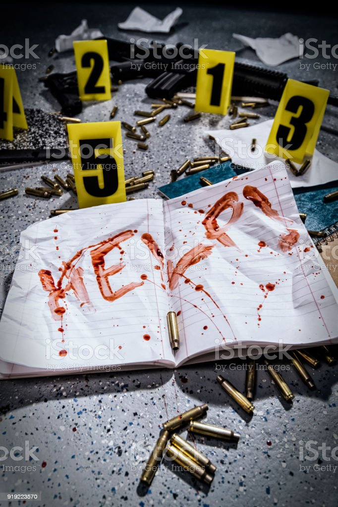 Notebook with HELP! written in blood and crime scene markers after a school shooting in America. stock photo