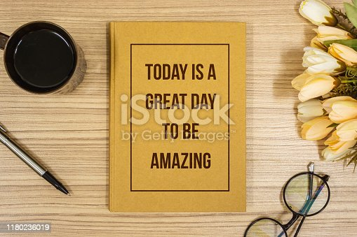 Overhead View of Notebook with Inspirational Quote on Wooden Work Desk. Be Amazing.