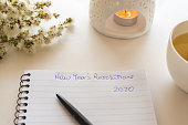 Close up of notebook and pen with handwritten New Year's Resolutions 2020 text on table with oil burner and flowers (selective focus)