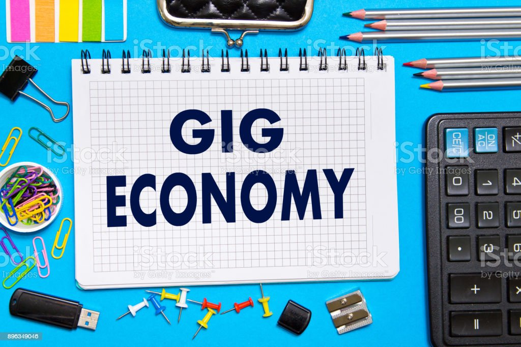 Notebook with Notes GIG ECONOMY office tools  on a blue background . Concept GIG ECONOMY stock photo