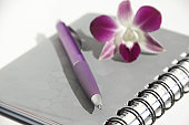 Notebook with pen and flower an orchid