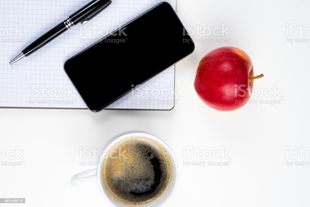Notebook with pencil white cup of coffee and a smartphone. - Royalty-free Business Stock Photo