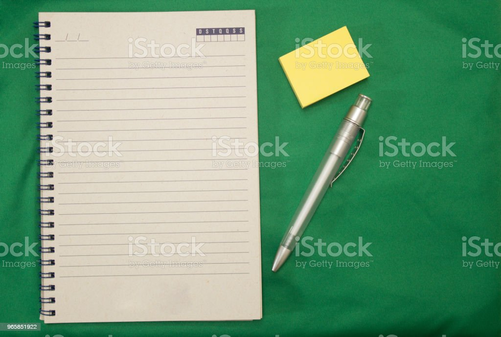 Notebook with spiral, transparent pen and yellow reminder block on green background - Royalty-free Blank Stock Photo