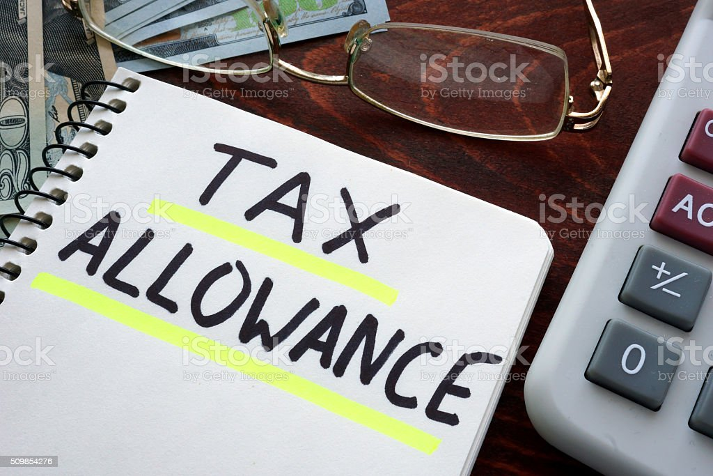 Notebook with tax allowances  sign on a table. stock photo