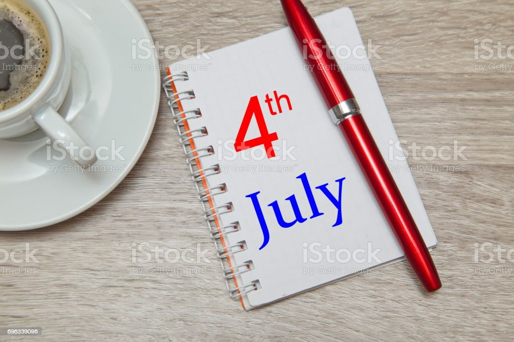 Notebook with text 4th of July and red pen stock photo