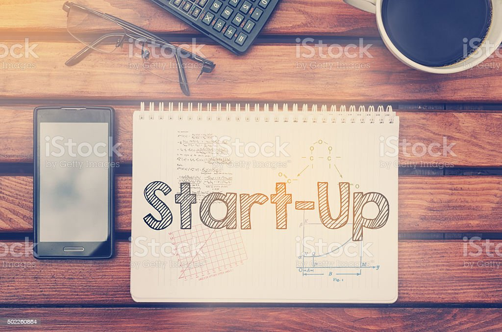 Notebook with text inside Start Up on table stock photo