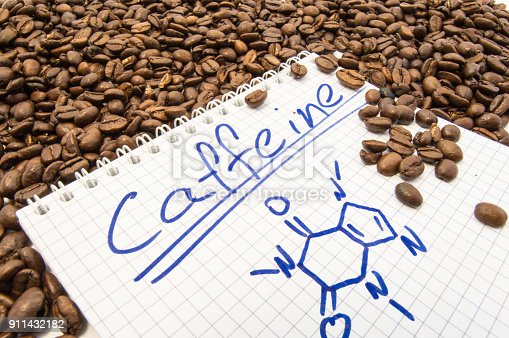 1175869940istockphoto Notebook with text title caffeine and painted chemical formula of caffeine is surrounded by fried ready to use grains of coffee beans. Visualization caffeine as main alkaloid of fruit of coffee tree 911432182