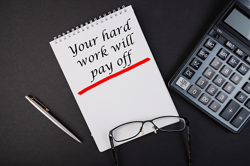 1044507110 istock photo Notebook with the inscription Your Hard Work Will Pay Off on a black table. 1205472450